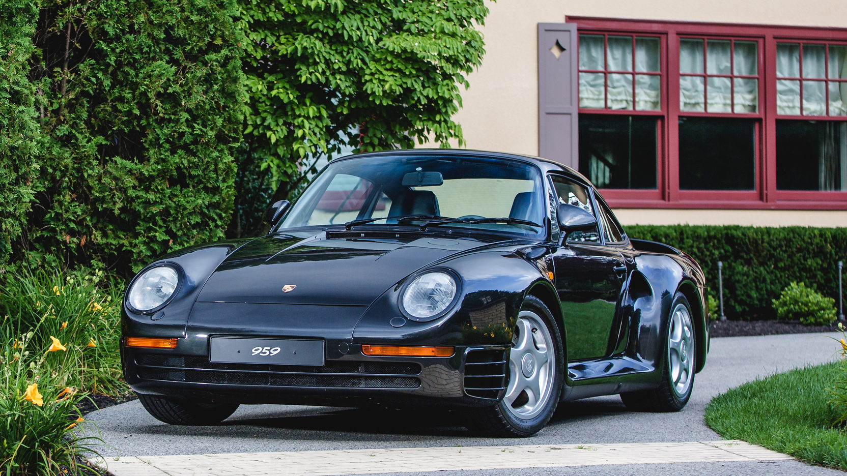 Black Porsche 959 sitting in driveway outside house