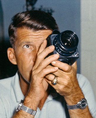 Wally Schirra with his space-bound Hasselblad 500c. We've got no idea why he's wearing two watches.