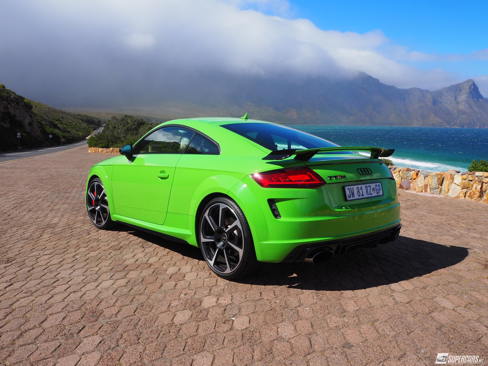 Green 2022 Audi TT-RS parked on side of road near ocean and mountains