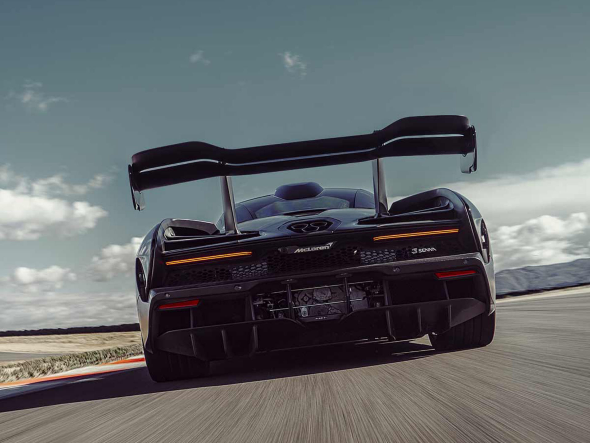 Rear view of black McLaren Senna being driven down track at high speed