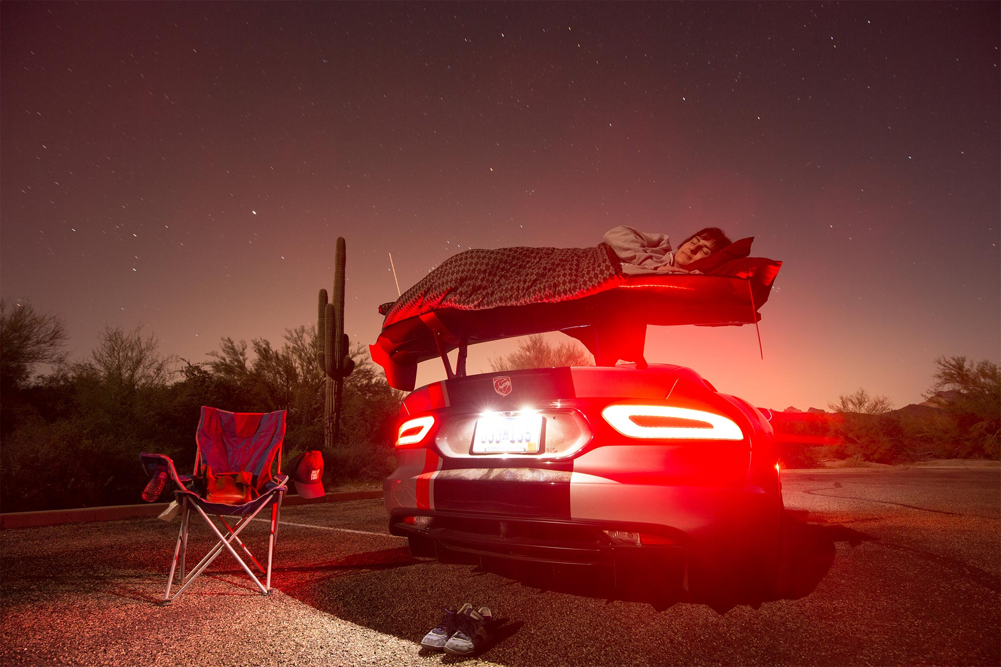 Driver in blanket lying on spoiler of 2016 Dodge Viper ACR and sleeping under stars