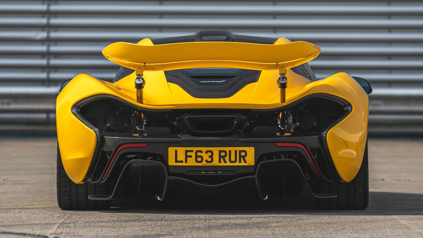 Rear view of yellow McLaren P1 outside garage