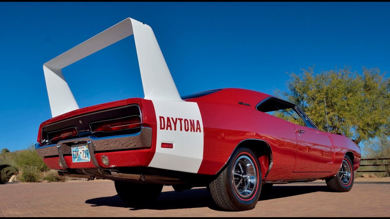 Red and white 1969 Dodge Charger Daytona sitting outside near tree