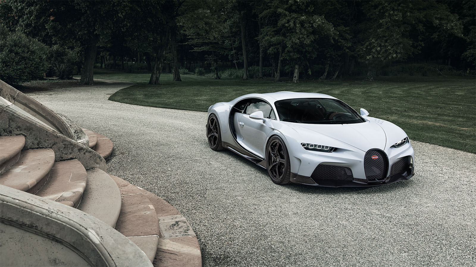 A view of a Bugatti Chiron parked at a driveway of a large staircase.