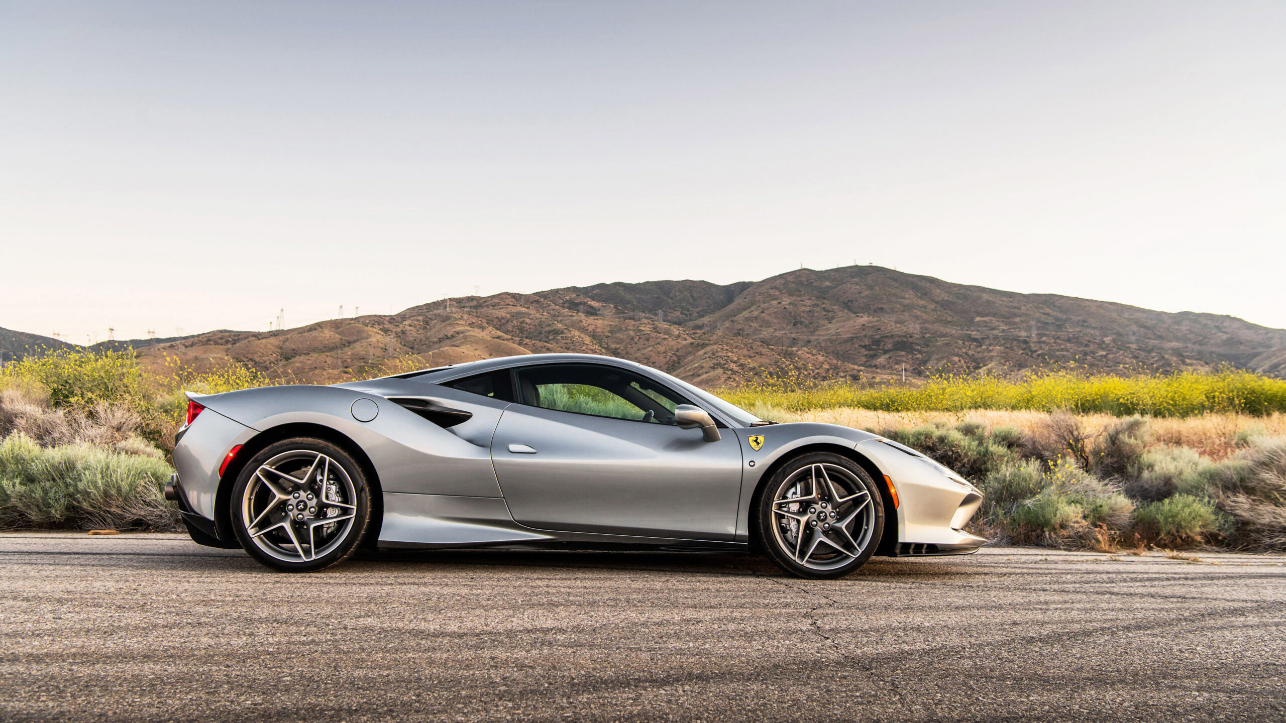 A side view of a silver Ferrari F8 Tributo, in the country.