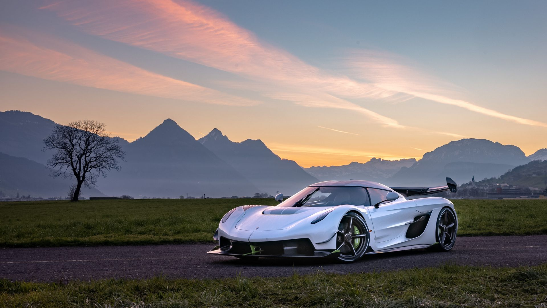A frontal side view of a Koenigsegg Jesko, in front of a rugged landscape.