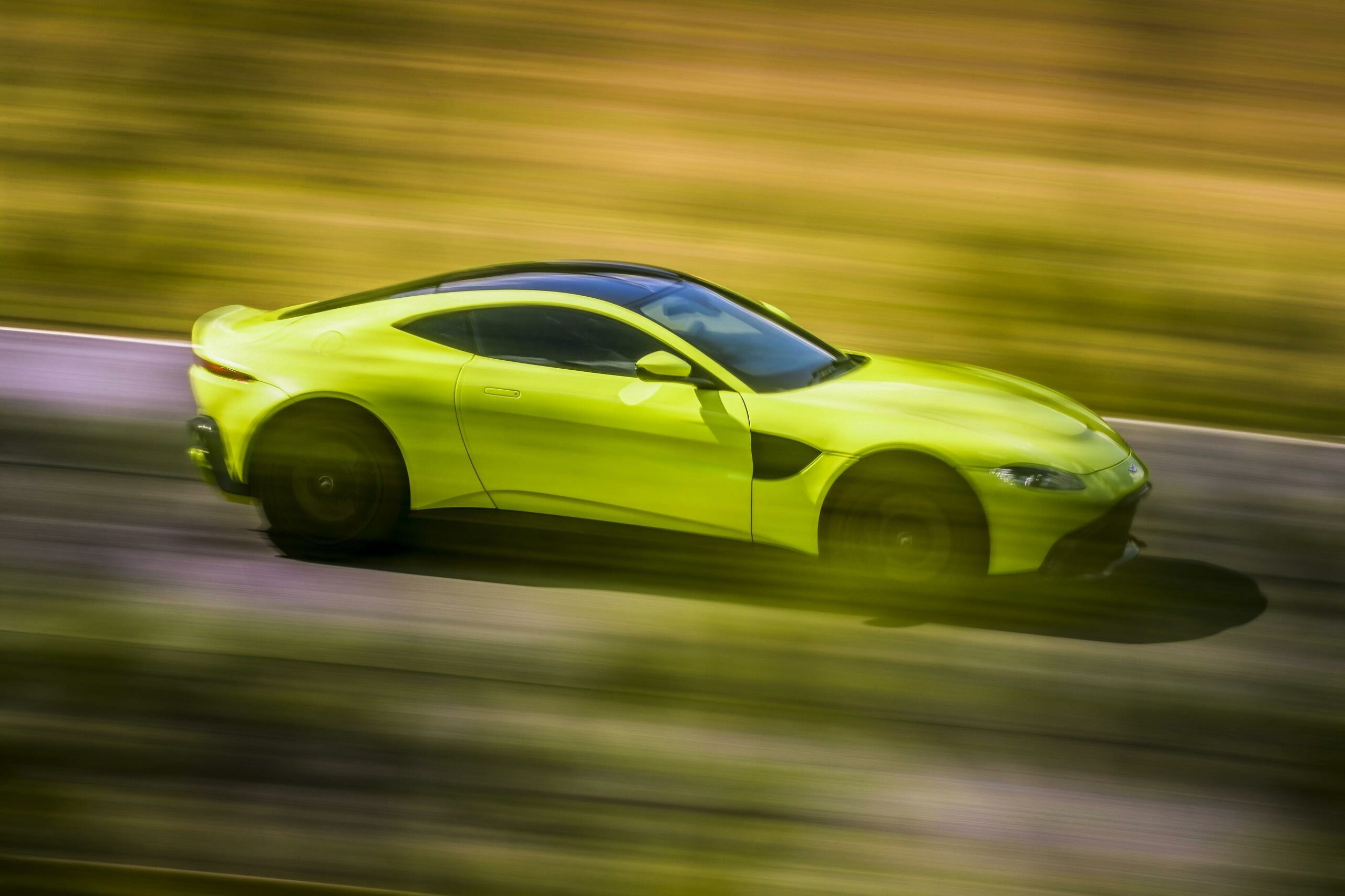 A side view of a neon yellow Aston Martin V8 Vantage driving down a road